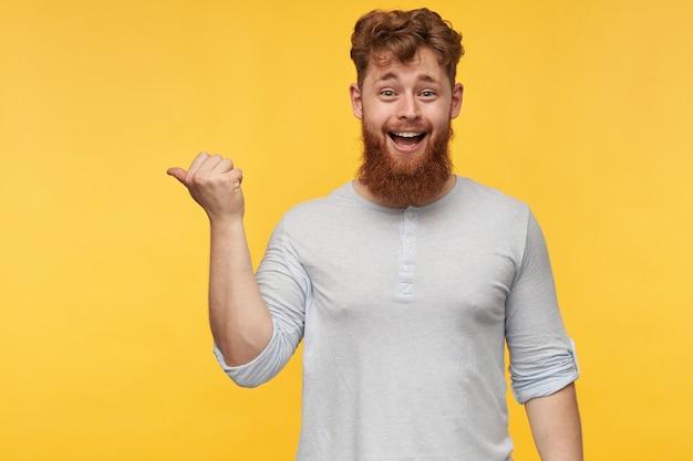 Portret van een jonge, bebaarde man met rood haar, voelt zich gelukkig en lacht terwijl hij naar de kopie ruimte aan de linkerkant op geel wijst.