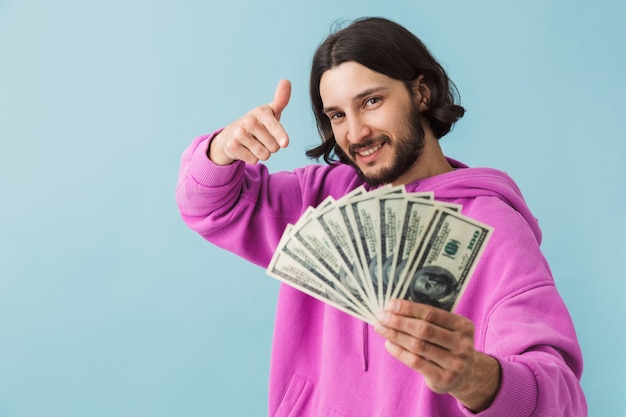 Portret van een jonge, bebaarde man met vrijetijdskleding die geïsoleerd over de muur staat, geldbankbiljetten toont, wijzende vinger