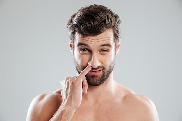 Portret van een jonge, bebaarde naakte man die zijn neus plukt