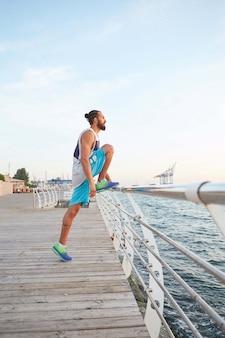 Portret van een jonge, bebaarde sportieve kerel die ochtendoefeningen doet aan zee, die zich uitstrekt voor de benen, opwarmen na het hardlopen.