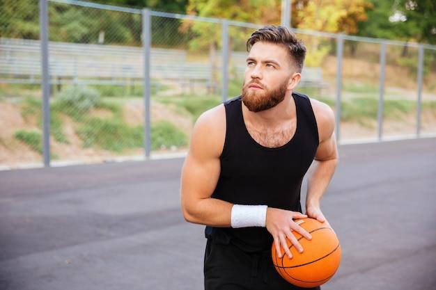 Portret van een jonge, bebaarde sportman die buiten basketbal speelt