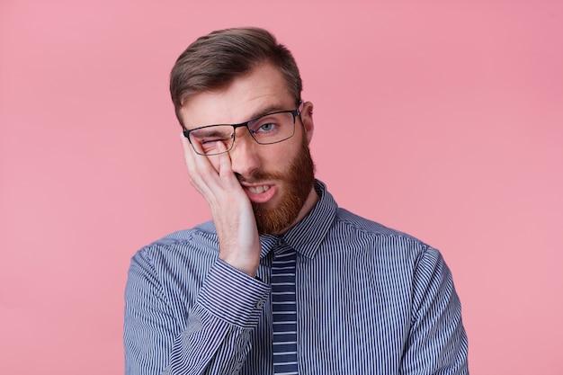 Portret van een jonge bebaarde zakenman draagt een bril voelt zich ongelukkig en moe, steunt zijn hoofd, geïsoleerd op roze achtergrond.