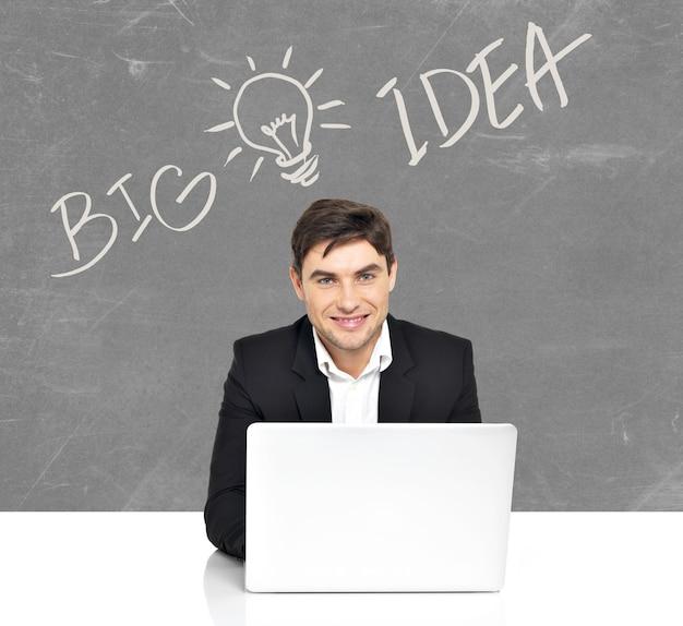 Portret van een jonge bedrijfsmens met laptop en ideeschets achter mannetje