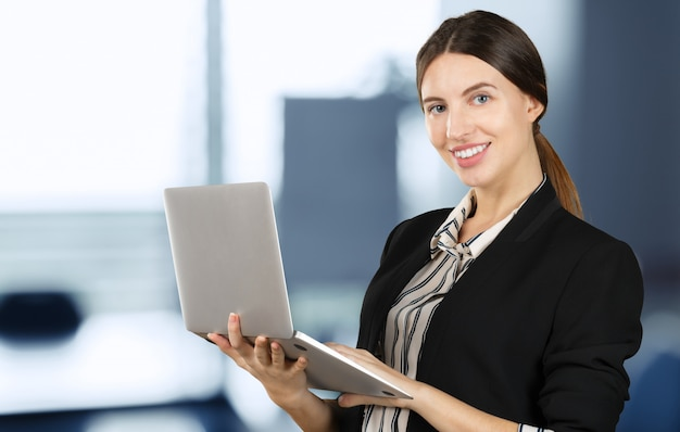 Portret van een jonge bedrijfsvrouw die laptop met behulp van