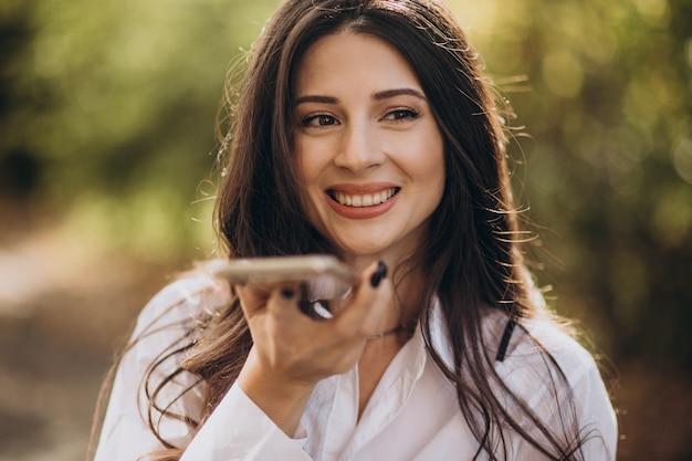 Portret van een jonge bedrijfsvrouw die telefoon met behulp van