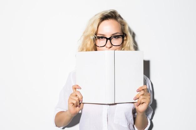 Portret van een jonge bedrijfsvrouw die zich achter een boek met bril verstopt, geïsoleerd op een grijze muur