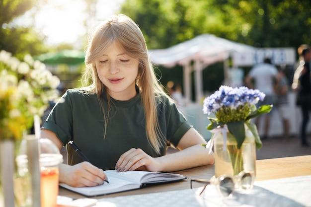 Portret van een jonge bedrijfsvrouw of student die haar plannen in kladblok schrijven die op een smartphone spreken