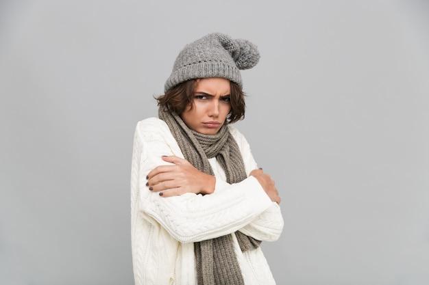 Portret van een jonge bevroren vrouw in sjaal en muts