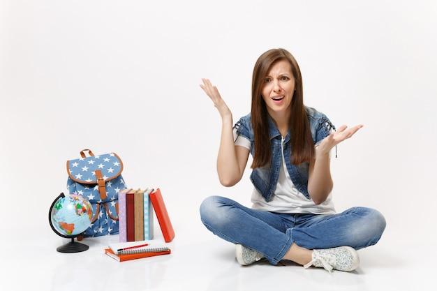 Portret van een jonge, bezorgde, geïrriteerde studente in spijkerkleding die handen uitspreidt die in de buurt van schoolboeken van de wereldrugzak zitten geïsoleerd