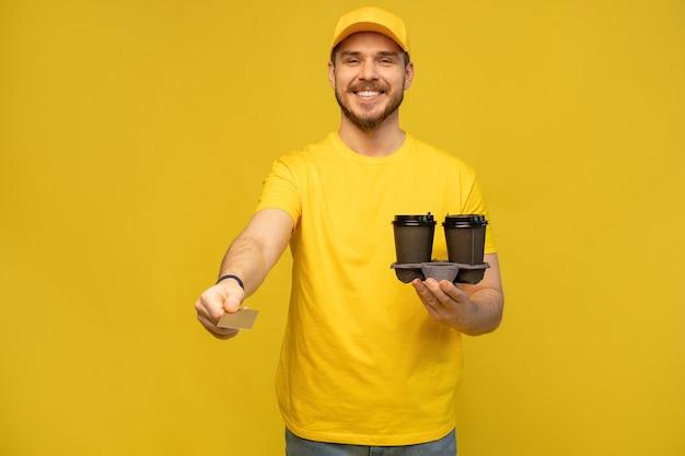 Portret van een jonge bezorger in geel uniform met afhaalkoffie geïsoleerd over gele muur
