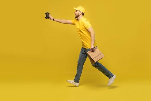 Portret van een jonge bezorger in geel uniform met papieren pakket en afhaalkoffie geïsoleerd over gele muur