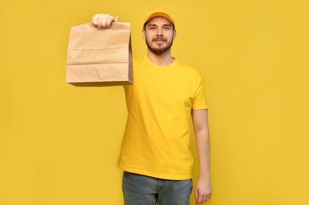Portret van een jonge bezorger in geel uniform met papieren pakket geïsoleerd over gele muur