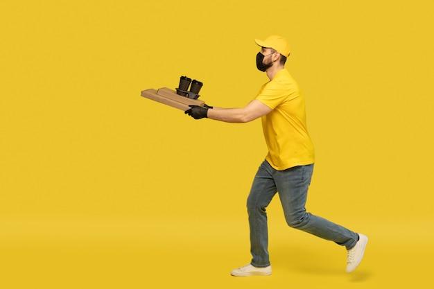 Portret van een jonge bezorger in geel uniform met pizzadozen en afhaalkoffie geïsoleerd