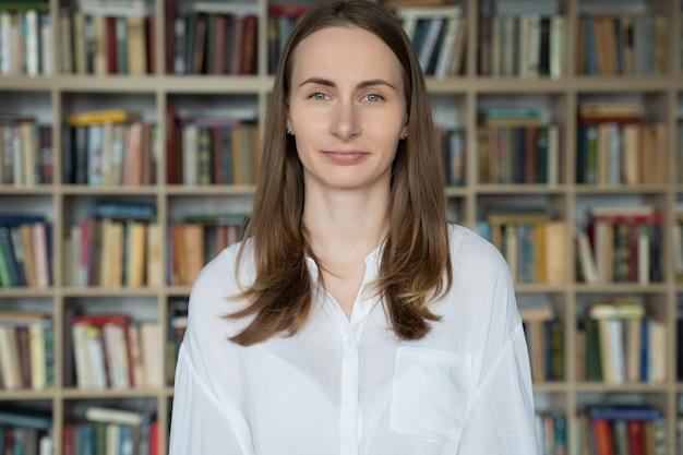 Portret van een jonge bibliothecaris vrouw lachend in bibliotheek boekenkast