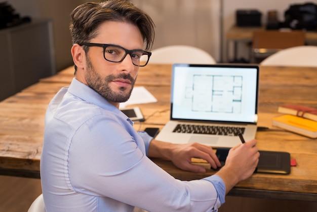 Portret van een jonge binnenhuisarchitect die op kantoor werkt. man aan het werk op laptop draaien. gelukkige architect die lay-out op laptop bij bureau en met tevredenheid bestudeert