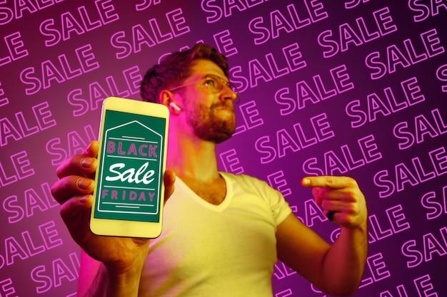 Portret van een jonge blanke man die het mobiele telefoonscherm toont op een paarse achtergrond met neonletters. concept van verkoop, zwarte vrijdag, cybermaandag, financiën, zaken. online winkels en betalingen factuur.