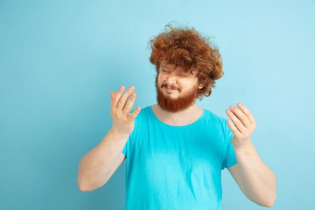 Portret van een jonge blanke man in zijn schoonheidsdag en huidverzorgingsroutine. mannelijk model met natuurlijk rood haar dat vochtinbrengende crème, oliën op de gezichtshuid toepast. lichaams- en gezichtsverzorging, natuurlijk, mannelijk schoonheidsconcept.