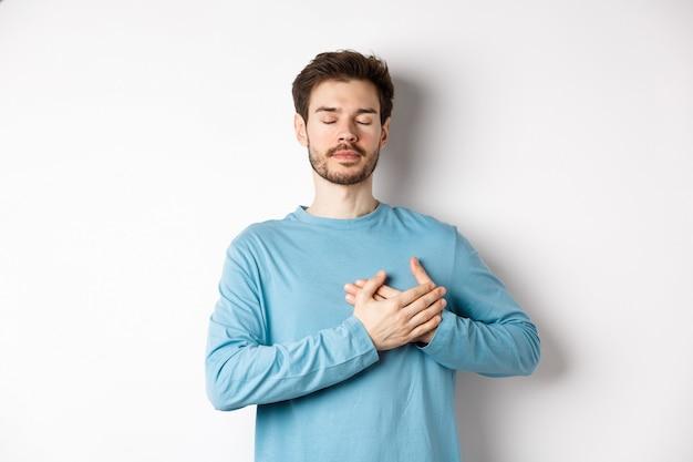 Portret van een jonge blanke man met baard staan met de handen op het hart en gesloten ogen, dromen over gelukkige momenten, staande op een witte achtergrond.