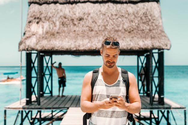 Portret van een jonge blanke man met rugzak met behulp van slimme telefoon en staande op dok.