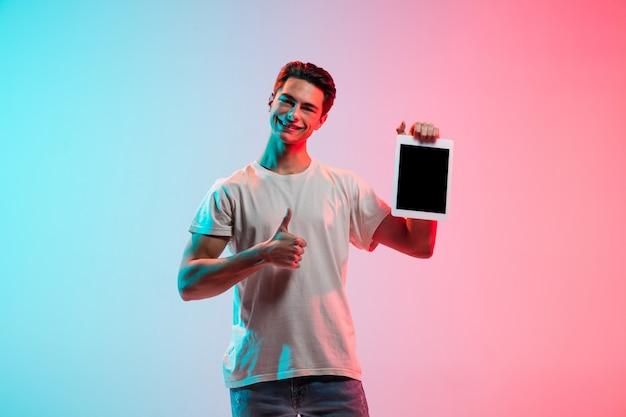 Portret van een jonge blanke man op een blauwroze studioachtergrond met kleurovergang in neonlicht