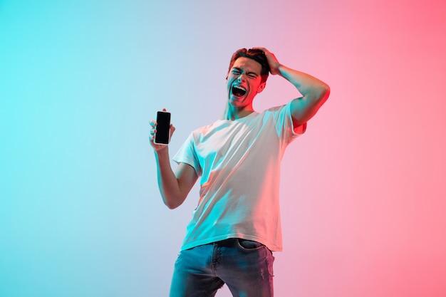 Portret van een jonge blanke man op kleurovergang blauw-roze studio in neonlicht