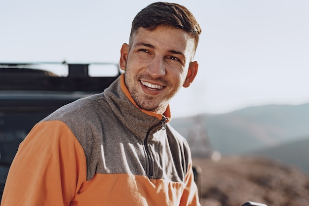 Portret van een jonge blanke man wandelen in de bergen close-up