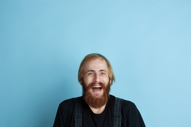 Portret van een jonge blanke man ziet er dromerig, schattig en gelukkig uit. opzoeken en denken aan blauwe ruimte