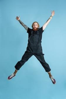 Portret van een jonge blanke man ziet er dromerig, schattig en gelukkig uit. springen. lachen op blauwe ruimte
