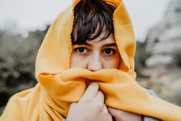 Portret van een jonge blanke vrouw bedekt met een gele sjaal