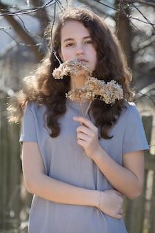 Portret van een jonge blanke vrouw. gelukkig mooi krullend meisjesclose-up, wind fladderend haar. lente portret buitenshuis.