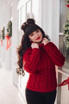 Portret van een jonge blanke vrouw in een warme gebreide rode trui buiten glimlacht