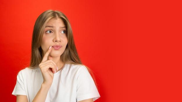 Portret van een jonge blanke vrouw met heldere emoties op een felrode studiomuur