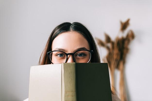 Portret van een jonge blanke vrouw student in oogglazen verstopt achter een boek