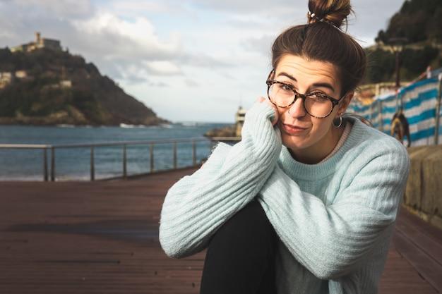 Portret van een jonge blanke vrouw zittend op een bankje aan zee