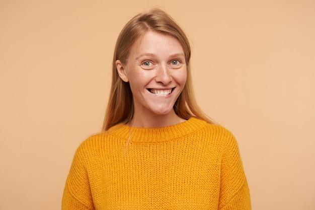 Portret van een jonge blije dame met losse foxyhaar met charmante glimlach en haar onderlip bijten, staande tegen beige