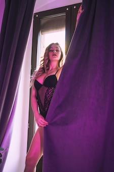 Portret van een jonge blonde blanke in ondergoed naast ramen gordijnen thuis. sensuele fotografie thuis