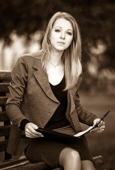 Portret van een jonge blonde dame in officiële zakelijke kleding zittend op een bankje in het park met het lezen van documenten op heldere zomerdag. mooi modern onderneemsterconcept