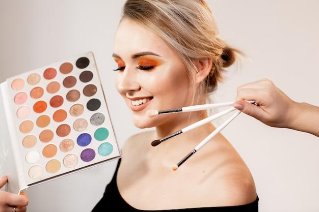 Portret van een jonge blonde glimlachende vrouw met een oranje-bruine heldere make-up en gesloten ogen. voor haar gezicht houden de handen verschillende make-upborstels en een schaduwpalet