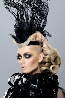 Portret van een jonge blonde meid die haar haar heeft en make-up gedaan voor een modeshow