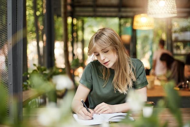 Portret van een jonge blonde student scenarioschrijver vrouw die haar eerste dramascript schrijft dat koffie drinkt in een café buitenshuis