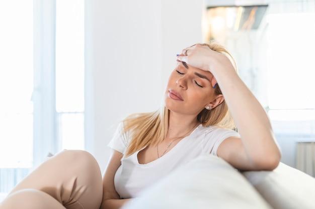 Portret van een jonge blonde vrouw die thuis op de bank zit met hoofdpijn en migraine. mooie vrouw die lijdt aan chronische dagelijkse hoofdpijn. treurige vrouw die haar hoofd vasthoudt omdat sinuspijn