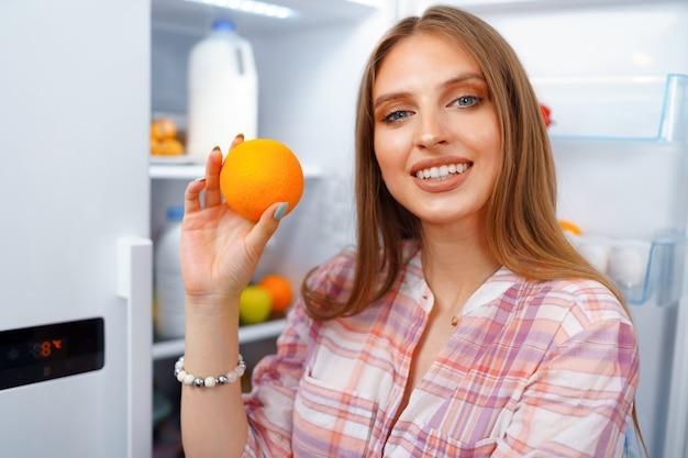 Portret van een jonge blonde vrouw die voedsel uit haar koelkast neemt