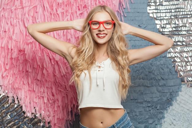 Portret van een jonge blonde vrouw met een rode bril die naar de camera kijkt