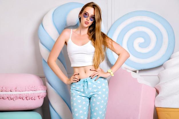Portret van een jonge blonde vrouw met lange haren, het dragen van leuke trendy pijama en zonnebril omringd door grote snoepjes