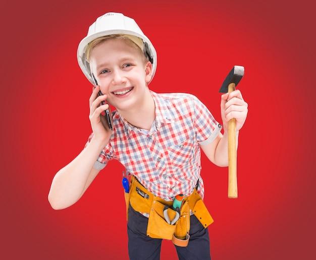 Portret van een jonge bouwer in een helm en een meetlint in zijn hand