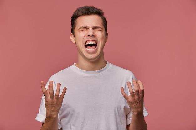 Portret van een jonge boze man in een leeg t-shirt, hoort slecht nieuws en ziet er slecht uit, staat op roze en schreeuwt met een ongelukkige uitdrukking.