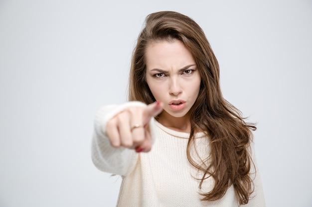 Portret van een jonge boze vrouw die met de vinger wijst naar camera geïsoleerd op een witte achtergrond