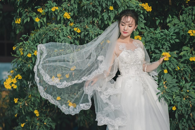 Portret van een jonge bruid draagt trouwjurk en witte sluier, staande op bloem