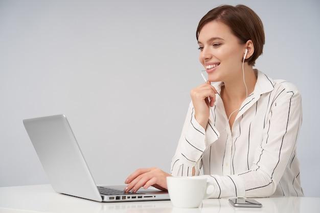 Portret van een jonge bruinharige vrouw met kort trendy kapsel die hand op toetsenbord vasthoudt terwijl ze op roze zit met laptop, gelukkig lacht en opgeheven hand onder haar kin houdt