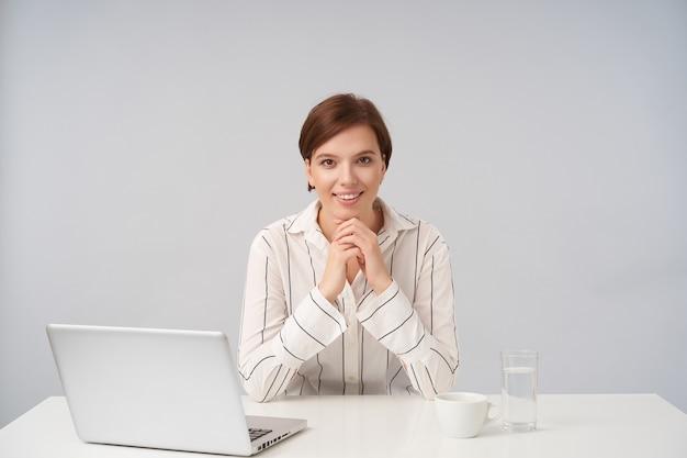 Portret van een jonge bruinogige kortharige brunette vrouw die gevouwen handen onder haar kin houdt terwijl ze positief kijkt met een charmante glimlach, geïsoleerd op wit
